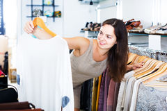 Girl in apparel store. Glad brunette girl selecting basic blouse in apparel store stock photography
