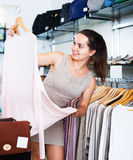 Girl in apparel store. Portrait of cheerful brunette girl selecting basic blouse in apparel store Stock Image