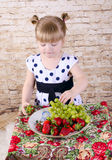 Girl with an appetite for eating fresh strawberries Royalty Free Stock Images