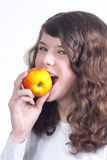 Girl with apple. Long haired girl biting an apple on a white background Stock Photos