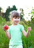 Girl with apple. Happy smiling girl with apple in a meadow Stock Photo