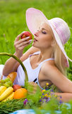 The girl with an apple. The girl on picnic with an apple in a hand Royalty Free Stock Photo