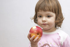 Girl with apple. Little girl eating healthy apple isolated on white Royalty Free Stock Image