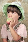 The girl with an apple. The little girl in a summer hat eats an apple Royalty Free Stock Image