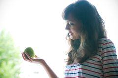 Girl with apple. A brunette girl holding an apple Royalty Free Stock Photo