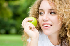 Girl And Apple. A pretty young woman outside in park holding an apple royalty free stock photography
