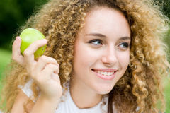 Girl With Apple. A pretty young woman outside in a park holding a green apple stock photography
