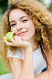 Girl With Apple. A pretty young woman outside in a park holding a green apple stock photo
