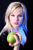Girl with apple. Under blue light against black background Stock Photo