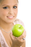 Girl with apple. Closeup portrait of beautiful girl holding a green apple, smiling. Selective focus on girl Stock Photos
