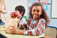 Girl with apple as a healthy snack. In break in elementary school stock image