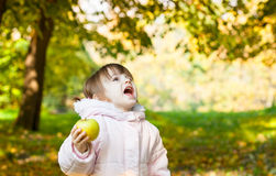 Girl with an apple in autumn park Stock Photo