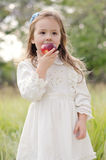 Girl and apple. Beautiful girl in white dress eating an apple in the autumn garden stock image
