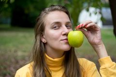Girl with apple. Beautiful woman lady girl holding big yellow apple, natural beauty face, relax in the garden autumn park. day picnic in the village, fresh air Stock Photography