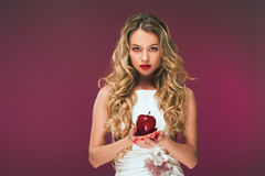 The girl with an apple. Beauty Photo of a beautiful young woman in a cocktail dress. Royalty Free Stock Images