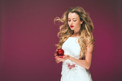 The girl with an apple. Beauty Photo of a beautiful young woman in a cocktail dress. Stock Photo