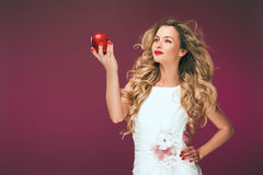The girl with an apple. Beauty Photo of a beautiful young woman in a cocktail dress. Royalty Free Stock Photography