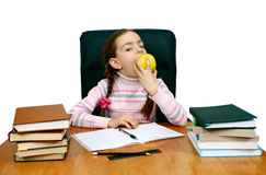 Girl with an apple being at a writing table Stock Images