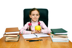 Girl with an apple being at a writing table Royalty Free Stock Image