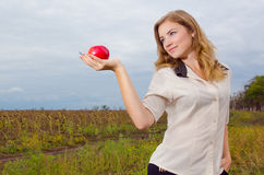 Girl with apple. Blondie girl holding an apple in the palm Stock Photography