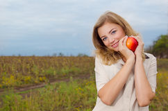 Girl with apple. Cute blonde girl with apple stock images