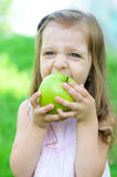 Girl with apple. Cute little girl with green apple outdoors Royalty Free Stock Image