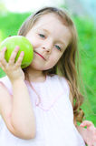Girl with apple. Cute little girl with green apple outdoors Royalty Free Stock Photo