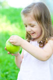 Girl with apple. Cute little girl with green apple outdoors Royalty Free Stock Images