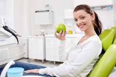 A girl with an apple in dentistry. The patient with a green apple in the clinic Stock Photo