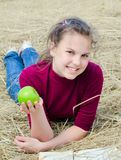 Girl with an apple on dry  grass Royalty Free Stock Photo