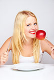 Girl with apple on fork Royalty Free Stock Image