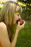 Girl with an apple on a green lawn Stock Photography