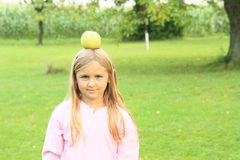 Girl with apple on head. Smiling little girl with yellow apple on head with blond hair Stock Photos