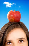 Girl with apple on her head Stock Image