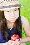 Girl with apple inflates cheeks Royalty Free Stock Photo