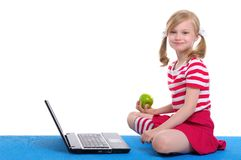 Girl with an apple and laptop sitting on rug Royalty Free Stock Photography