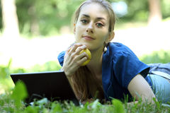 Girl with an apple lies on a grass in the summer Stock Photos