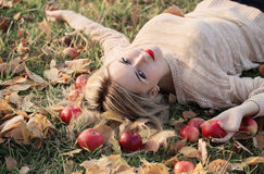 Girl with the apple is lying on the grass Royalty Free Stock Photo