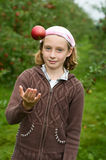 Girl in an apple orchard. Young girl throwing an apple in the air in an apple orchard Royalty Free Stock Photos