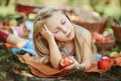 Girl with Apple in the Apple Orchard. Beautiful Girl Eating Organic Apple in the Orchard. Harvest Concept. Garden, Toddler eating stock image
