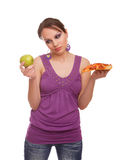 Girl with apple and pizza making a decision Stock Photo