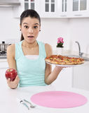 Girl apple and pizza unstable Royalty Free Stock Image