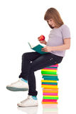 Girl with apple siting on books Stock Photo