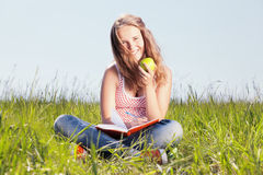 Girl with an apple. Girl sits on a grass and eats a green apple Royalty Free Stock Images