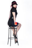 Girl with apple on stool Stock Images