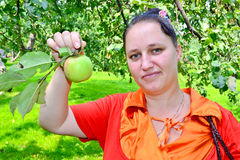 The girl with an apple. Girl with torn fresh apple in the garden stock photos