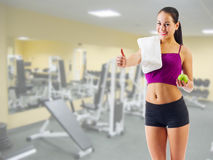 Girl with apple and towel at fitness club Royalty Free Stock Image