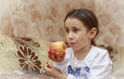 Girl with an apple. The girl is watching TV and eating an apple Stock Photography