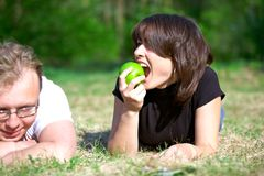 Girl with an apple and a young man Stock Photo