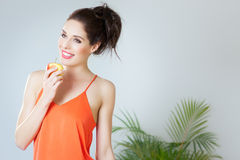 Girl With Apple. Young girl with red apple. Orange color. Healthy eating concept indoors Royalty Free Stock Image